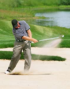 man hitting golf ball out of sandtrap